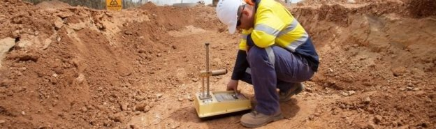 Geotechnical engineer testing soil on construction site